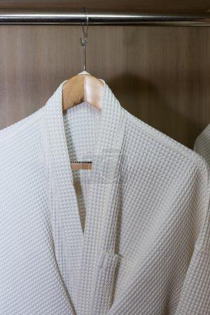 Photo pour Peignoirs blancs suspendus dans un placard en bois - image libre de droit