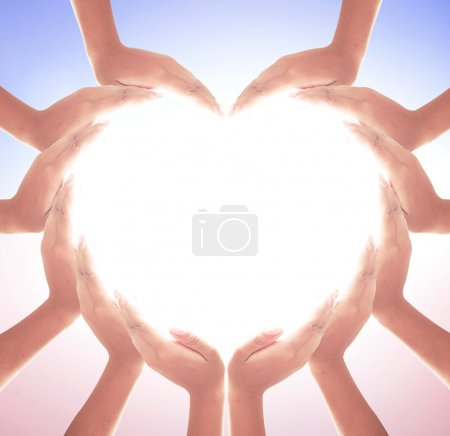 Human hands in shape of heart on blurred nature ba...