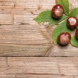 Chestnuts on a brown wooden table with some leaves...