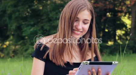 Joyful girl working on the tablet in social networks.