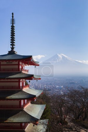 Mt. Fuji viewed from behind red Chureito Pagoda with clear blue sky
