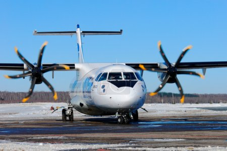 The passenger ATR-72 plane of the company Utair the Express with the rotating propellers