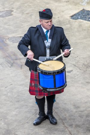 Photo pour Le batteur musicien écossais d'une fanfare sert d'hôte à l'arrivée de navires transatlantiques dans le port d'Invergordon en Écosse comité . - image libre de droit