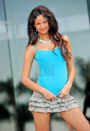 "Blue Top - Gray Frilly Skirt - Slim Brunette - ""Reflexed Palm Tree"" Background"