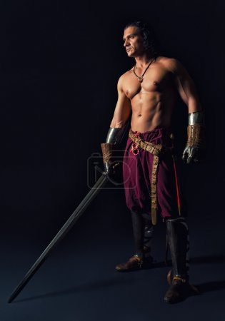 Photo for Half-naked man with a sword in medieval clothes on a dark background - Royalty Free Image