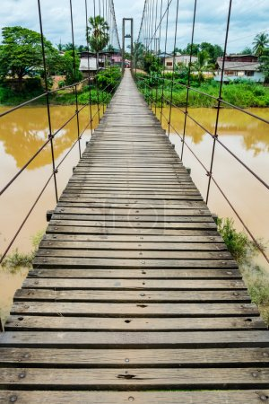 Photo for Rope suspension bridge across a river in flood, Thailand - Royalty Free Image