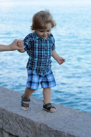 Boy walking near sea