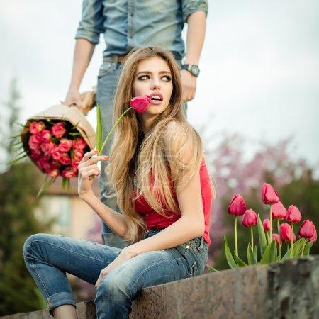 Photo pour Jeune femme s'assoit sur un banc et attendre à l'homme debout à côté d'elle, l'homme qui lui donne un bouquet de rose - image libre de droit