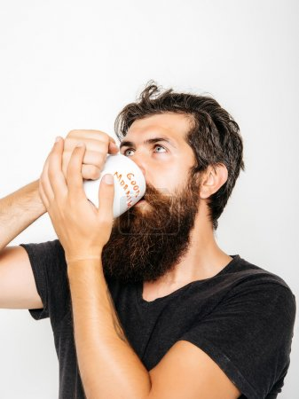 bearded serious man with cup of coffee or tea