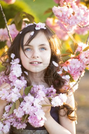 Photo for Little brunette girl looking upwards standing amid pink japanese cherry blooming in broad daylight in the park, vertical picture - Royalty Free Image