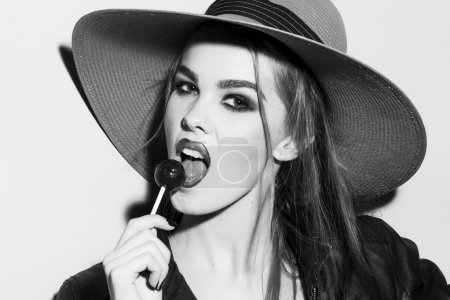 Wild young blonde woman black and white portrait with sugar candy