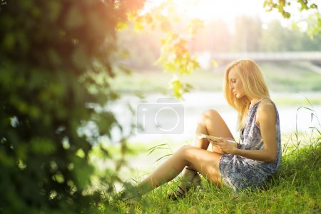 Photo for Beautiful sexual blond woman sitting outdoor with book in summer on green natural background, horizontal picture - Royalty Free Image