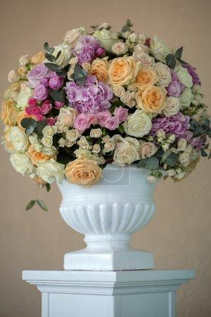 Foto de Decorar el ramo de Novia de frescas flores de rosas y peonía blanca rosa violeta morado lila y naranja colores amarillos en Jarrón grande sobre fondo beige, imagen vertical - Imagen libre de derechos