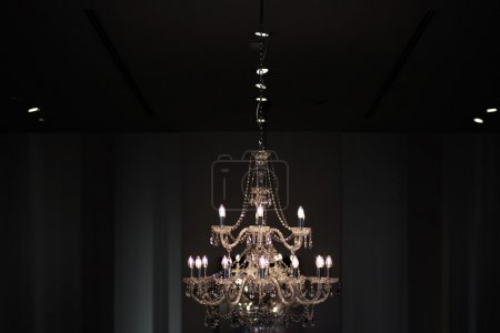 Foto de Closeup of one big beautiful old electric chandelier with candles and lots of decorative crystal beads hanging on ceiling and brightly lit on dark indoor background, horizontal picture - Imagen libre de derechos