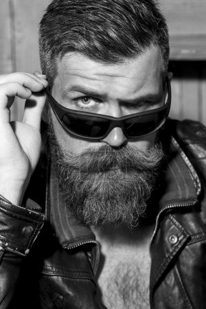 Foto de Portrait of handsome brutal unshaved man with long beard and moustache in leather biker jacket and sunglasses looking forward black and white closeup, vertical picture - Imagen libre de derechos
