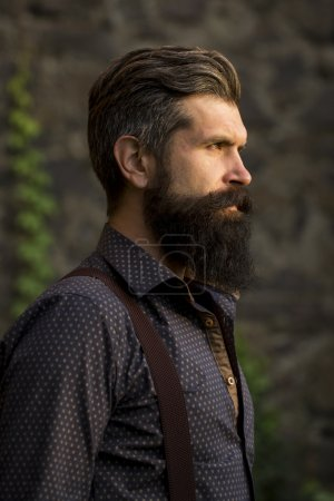 Photo for Closeup side view of one handsome senior man with black hair and long lush beard in blue shirt and purple trausers standing outdoor on stone wall grey background, vertical picture - Royalty Free Image