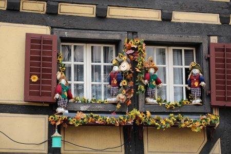 Photo pour Closeup façade de fond de maison avec doubles jumeaux vieille fenêtre avec volets ouverts en bois décoré avec des fleurs artificielles feuilles d'automne et des figures d'épouvantails de conte de fées, image horisontale - image libre de droit