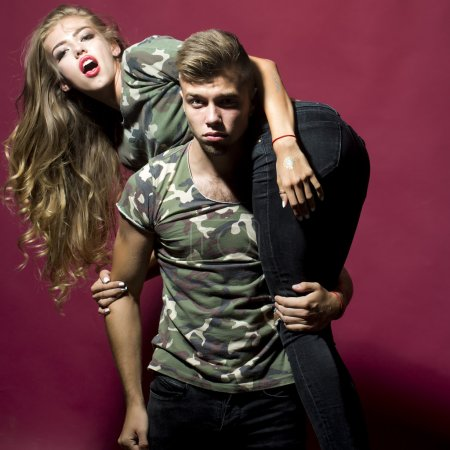 Photo for Strong brutal handsome blonde man carry on shoulders glamour seductive attractive woman with fashion makeup long beautiful hair dressed in camouflage t-shirts jeans studio on purple background, square - Royalty Free Image