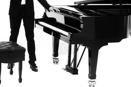 Photo pour Vue rapprochée d'une belle grande forte piano ouvert noir brillant avec clavier blanc et musicien masculin debout en studio isolé sur fond blanc, image horizontale - image libre de droit