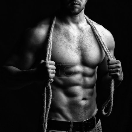 Photo for One handsome sexual strong young man with muscular body in blue jeans holding rope with hands hanging on neck and shoulders standing posing in studio black and white, square picture - Royalty Free Image