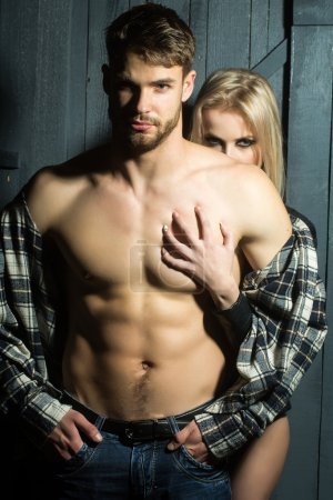 Photo for Young sexual couple of handsome serious man in checkered shirt with bare muscular chest standing before pretty blonde woman embracing and touching breast in studio, vertical picture - Royalty Free Image