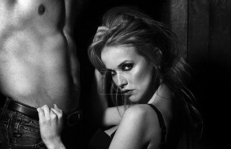 Photo pour Jeune couple sexuel de jolie femme blonde en soutien-gorge toucher et assis près de poitrine musclée nu bel homme et torse en studio sur fond en bois, photo carré - image libre de droit