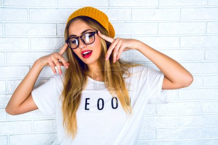 Photo for Fashion studio portrait of pretty young hipster blonde woman with bright sexy make up and glasses , wearing stylish urban t shirt and hat, White urban wall background - Royalty Free Image