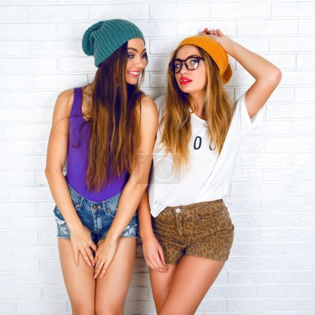 Photo for Funny fashion portrait of two stylish sexy hipster girls best friends, wearing cute swag outfits and hats, going crazy and showing piece science. Urban white brick wall background - Royalty Free Image