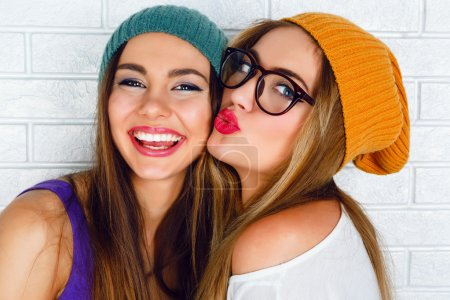 Photo for Close up fashion lifestyle portrait of two young hipster girls best friends, wearing bright make up and similar trendy hats, making funny faces and have gray time. Urban white brick wall background - Royalty Free Image