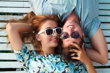 Photo for Fashion lifestyle portrait of young perfect couple lay and relaxed on their vacation, wearing sunglasses and vintage clothes, bright sunny summer colors - Royalty Free Image
