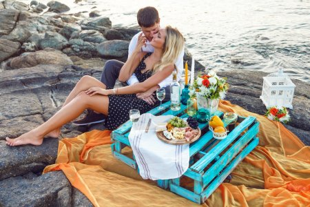 couple enjoying picnic on the beach together
