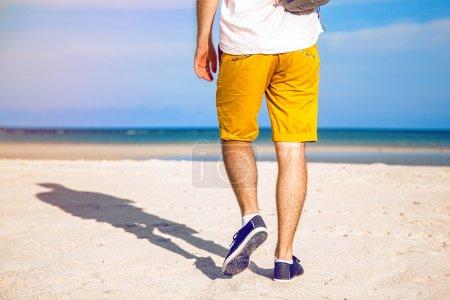 stylish man walking alone the beach
