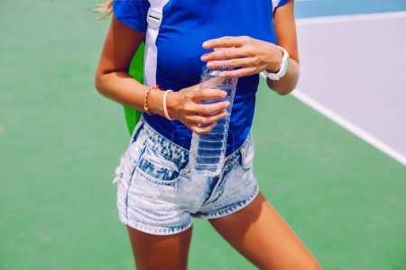 sportive girl holding bottle of water