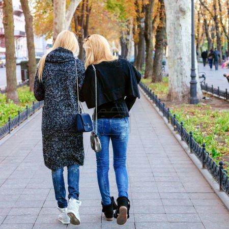 Photo pour Deux jolies filles marchant dans la rue à belle journée ensoleillée d'automne, portant des tenues décontractées hipster décontractées élégantes . - image libre de droit