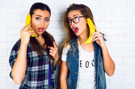 girls playing with bananas imitating telephone