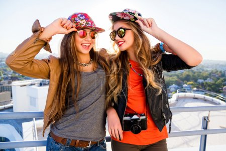 Photo for Two sisters posing on the roof, wearing stylish leather jackets swag hats and sunglasses, holding retro camera, ready for shooting, positive emotions. fashion portrait of best friends girls - Royalty Free Image