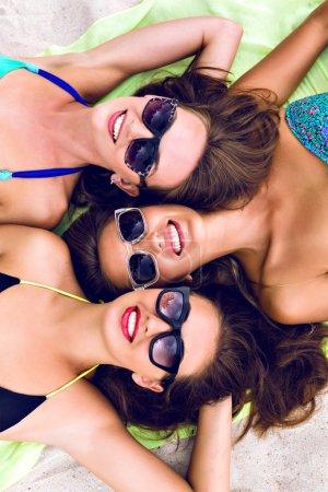 three girls laying on the beach