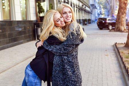 Photo pour Image extérieure de deux jolies meilleures amies filles blondes câlins dans la rue. Portrait de mode de deux soeurs blondes élégantes - image libre de droit