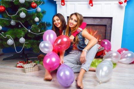 sisters posing near Christmas tree and fireplace