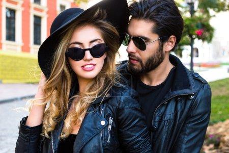 Photo pour Gros plan portrait de mode en plein air de jeunes jolis couples élégants dans les câlins d'amour dans la rue de la vieille ville, portant des vêtements en cuir noir total élégant rock n roll, lunettes de soleil et chapeau - image libre de droit