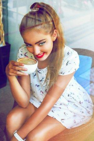 Photo pour Portrait de mode en plein air de jeune jolie fille avec de beaux grands yeux de colle, portant pin up tenue stylisée et maquillage, profiter de sa matinée parfaite avec une tasse de café sur la terrasse chic cafétéria minable - image libre de droit