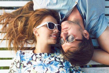 Photo pour Mode style de vie portrait de jeune couple parfait couché et détendu sur leurs vacances, portant des lunettes de soleil et des vêtements vintage, couleurs d'été ensoleillées lumineuses - image libre de droit
