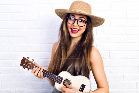 Hipster girl playing on small guitar