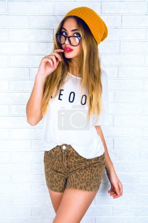 Photo for Indoor studio fashion portrait of stylish hipster woman wearing sexy shorts funny t-shirt glasses and hat. Surprised emotions. White urban background, bright colors - Royalty Free Image