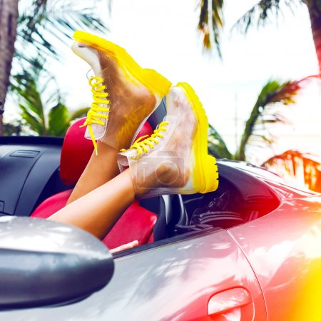 Photo for Outdoor fashion image of female legs in creative clear boots, laying at luxury car, palms, hot tropical country. Bright colors - Royalty Free Image