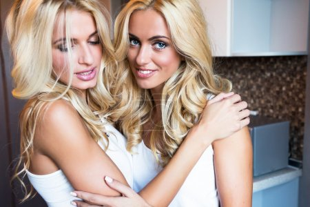 smiling blonds hugs at kitchen