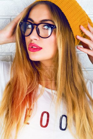 Photo for Close up bright fashion portrait of stylish hipster girl in glasses and hat, have sexy smile , full red lips and long blonde hairs, white background - Royalty Free Image