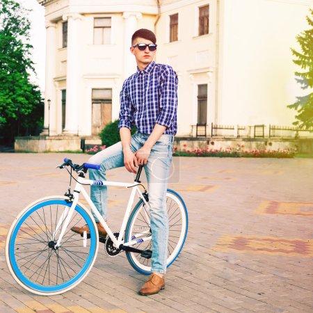 Hipster man posing on blue bike