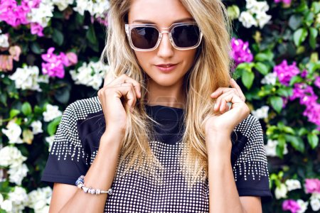 Photo for Young gorgeous stunning blonde young woman, wearing stylish outfit, trendy sparkled crop top and sunglasses, posing in floral garden background, beautiful summer day - Royalty Free Image