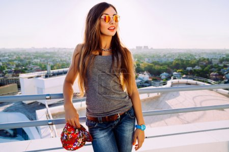 Photo for Young pretty fit sportive stylish girl with long brunette hair posing at the roof, wearing casual outfit swag hat and mirrored sunglasses, amazing view on the city, evening sunlight - Royalty Free Image